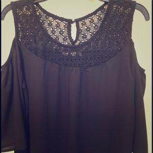 Black blouse with open shoulder sleeves.